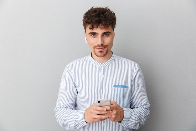 カメラを見て、灰色の壁に隔離された携帯電話を保持しているイヤポッドを持つ若い男の肖像画