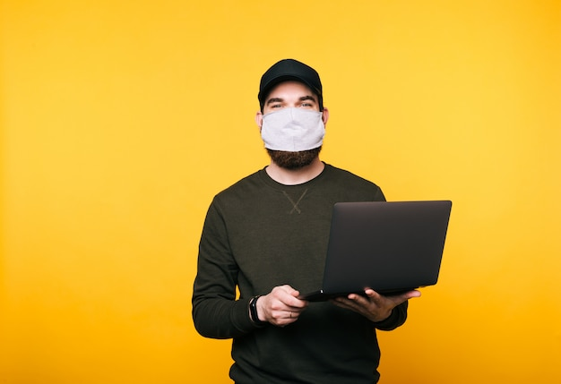 ラップトップを使用して顔のマスクを持つ若い男の肖像