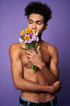 Портрет молодого человека с цветами, позирующего на фиолетовом фоне, чувственный мальчик-трансгендер стоит