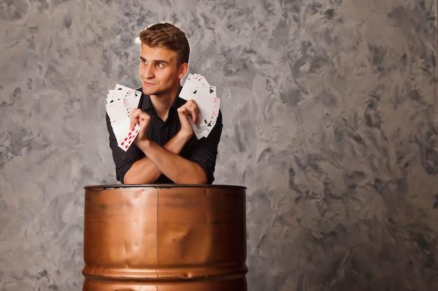 Портрет молодого человека с азартными играми из бочки. красивый парень показывает фокусы с картой.