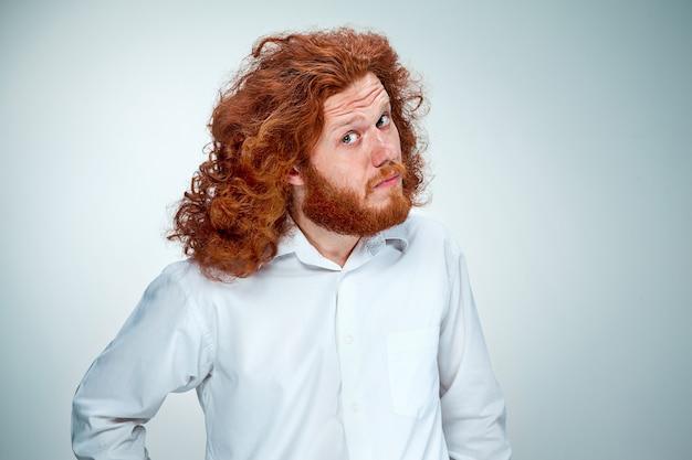 Портрет молодого человека с длинными рыжими волосами и шокированным выражением лица на сером фоне