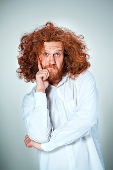 長い赤い髪と灰色の背景にショックを受けた表情を持つ若い男の肖像画