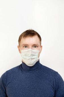 Портрет молодого человека с медицинской маской и испуганным взглядом на белом фоне с копией пространства