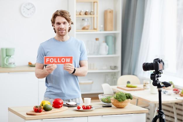 Портрет молодого человека с плакатом, улыбаясь в камеру и снимая блог для своих последователей на домашней кухне