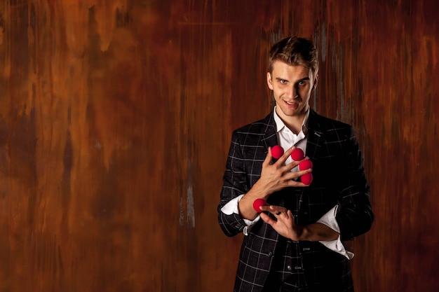 Портрет молодого человека с красными волшебными шарами. красивый парень показывает трюки с мячами. умные руки фокусника