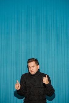 青いスタジオの背景の上にokを示す深刻な表情を持つ若い男の肖像画