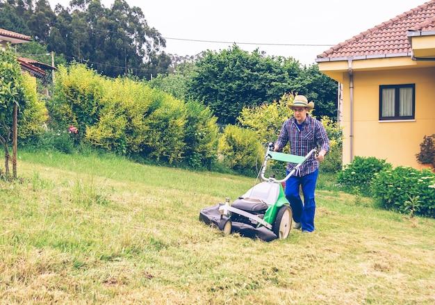 芝刈り機で芝生を刈る麦わら帽子と格子縞のシャツを持つ若い男の肖像画