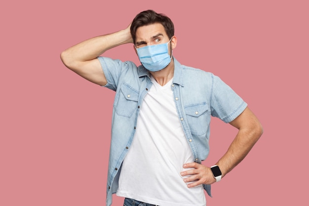 青いカジュアルなスタイルのシャツに立って、頭を掻き、目をそらし、何をすべきかを考えている外科用医療マスクを持つ若い男の肖像画。ピンクの背景に分離された屋内スタジオショット。
