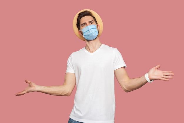 Портрет молодого человека с хирургической медицинской маской в белой рубашке с шляпой, стоящей с поднятыми руками и смотрящей в камеру с серьезным лицом. крытая студия выстрел, изолированные на розовом фоне copyspace.