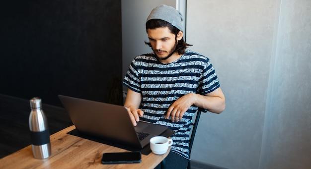 ノートパソコンで家で働く若い男の肖像画。スマートフォン、スチール製魔法瓶、コーヒーカップをテーブルに。