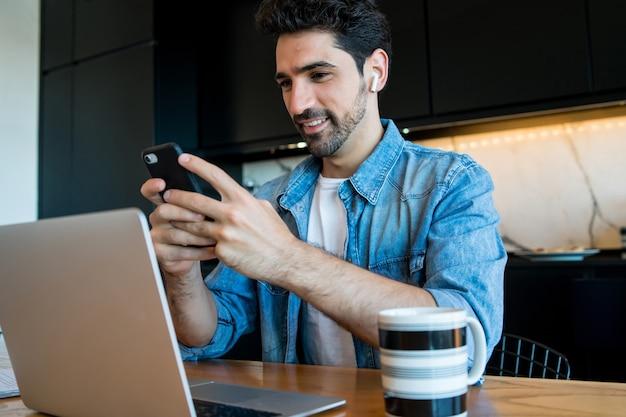 ラップトップで作業し、自宅から彼の携帯電話を使用して若い男の肖像画。ホームオフィスのコンセプト。新しい通常のライフスタイル。