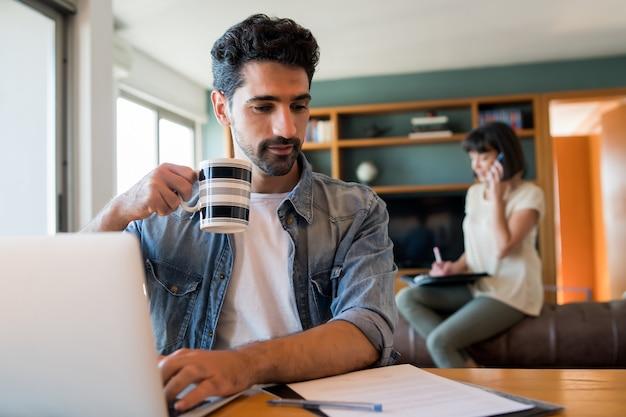 Портрет молодого человека, работающего с ноутбуком из дома, пока женщина разговаривает по телефону