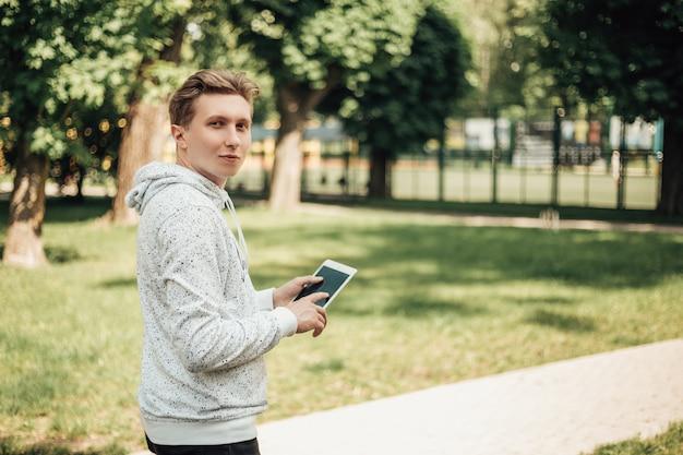 Портрет молодого менеджера или генерального директора, держащего белый планшетный компьютер с черным сенсорным экраном. мужчина в повседневной одежде стоит на улице в солнечный день с портативным гаджетом. изображение с копией пространства.