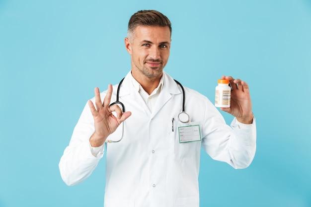 青い壁の上に孤立して立って、錠剤の瓶を保持している白いコートを着ている若い医療専門家の肖像画