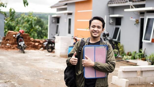 확인 제스처와 파일을 들고 그들의 새 집 앞에 서있는 젊은 남자의 초상화