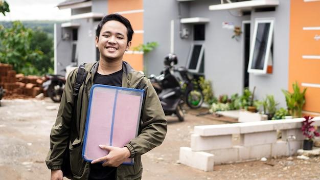 파일을 들고 그들의 새 집 앞에 서있는 젊은 남자의 초상화