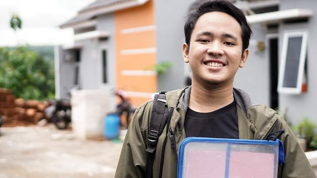 ファイルを保持している彼らの新しい家の前に立っている若い男性の肖像画