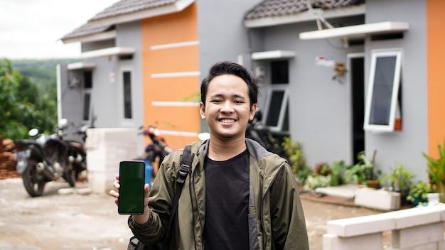 緑の電話を持っている彼らの新しい家の前に立っている若い男性の肖像画