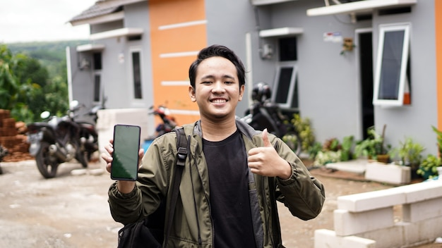 녹색 스크린 전화 확인 제스처와 함께 그들의 새 집 앞에 서있는 젊은 남자의 초상화