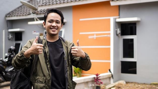 확인 제스처와 함께 그들의 새 집 앞에 서있는 젊은 남자의 초상화