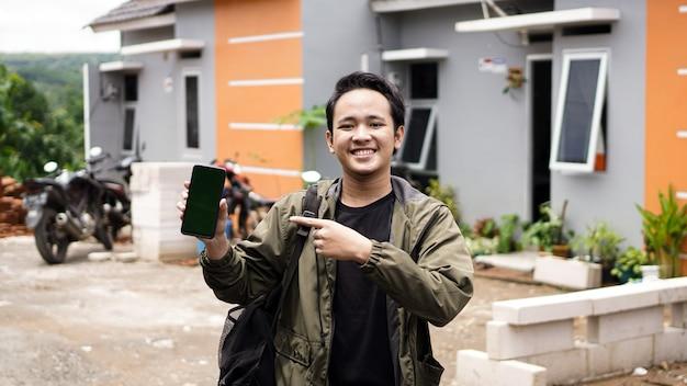 ポインティンググリーンスクリーン電話で彼らの新しい家の前に立っている若い男性の肖像画