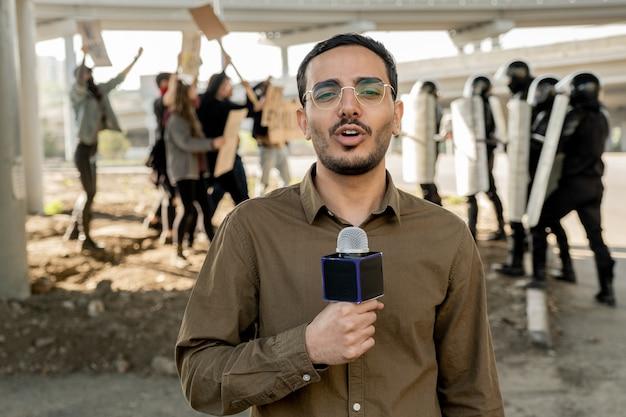 Портрет молодого журналиста смешанной расы с бородой, говорящего в микрофон во время освещения беспорядков: протестующие спорят с омоном на заднем плане