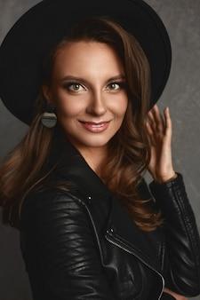 검은 유행 모자와 가죽 재킷에 밝은 메이크업과 완벽한 피부를 가진 젊은 모델 여자의 초상화