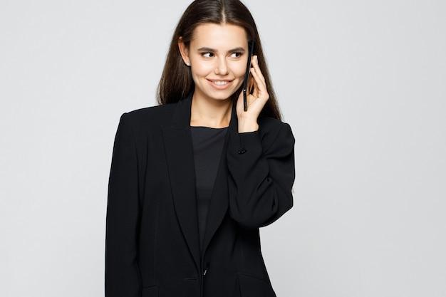 スマートフォンで話している古典的なスーツの若い現代ビジネス女性の肖像画