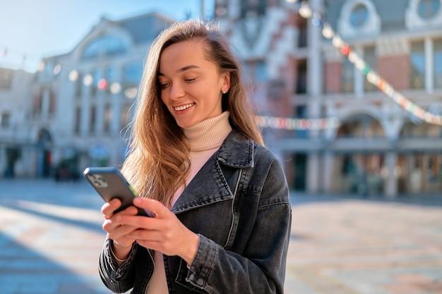 Портрет молодой современной случайной привлекательной кавказской счастливой радостной женщины, держащей и использующей телефон на открытом воздухе