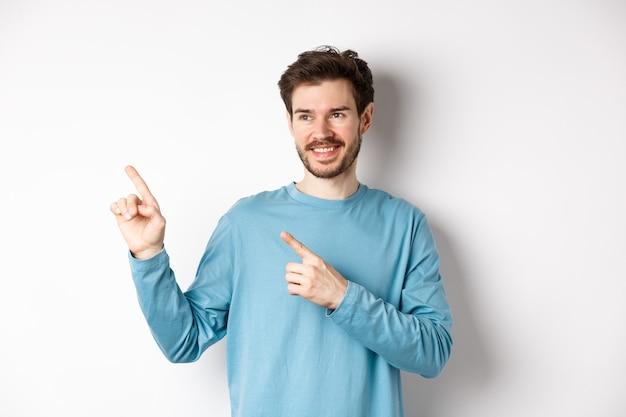 파란색 셔츠에 현대 젊은이의 초상화 왼쪽 상단 모서리에서 손가락을 가리키고 멀리보고, 흰색 바탕에 광고를 보여주는 만족 미소.