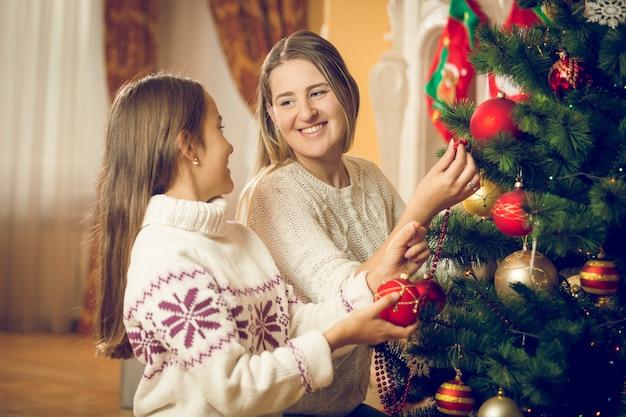 クリスマスツリーを飾る若い母と娘の肖像画