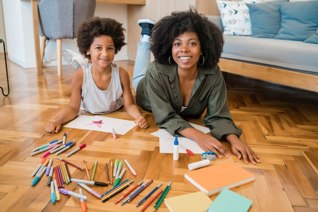 自宅の暖かい床に色鉛筆で描く若い母と息子の肖像画