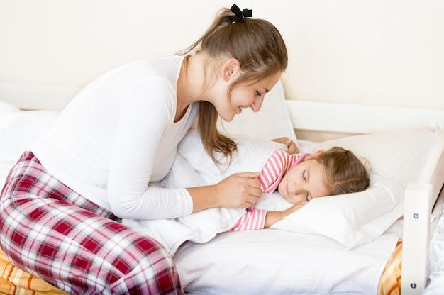 Портрет молодой матери, покрывающей маленькую спящую девочку одеялом