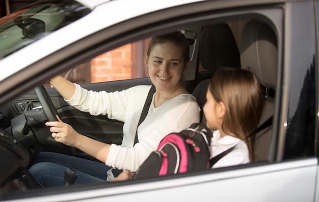 朝に娘を学校に運転する若い母親の肖像画