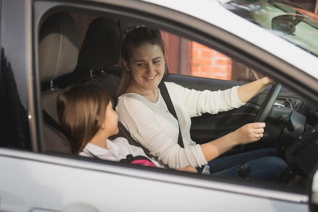 娘を学校に運転する若い母親の肖像画