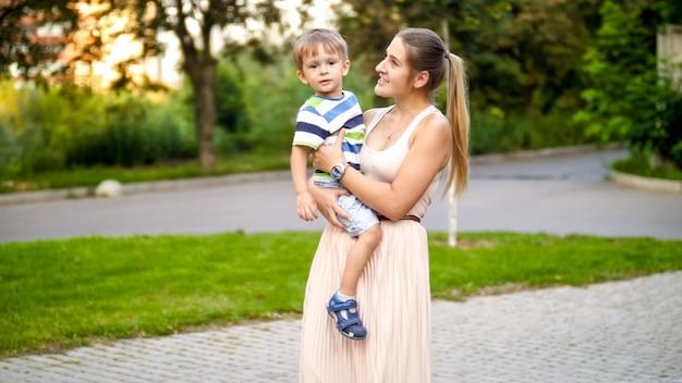 公園を歩きながら 3 歳の幼児の男の子を抱き、支える若い母親のポートレート