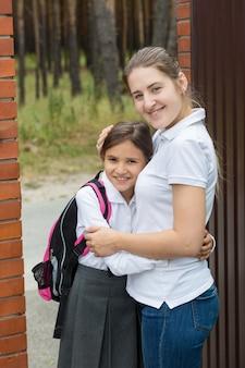 学校に見送る前に娘を抱き締める若い母親の肖像画