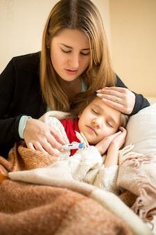 ベッドで病気の女の子を抱き締める若い母親の肖像画