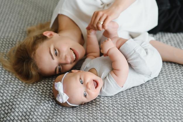 Портрет молодой матери с милым ребенком дома