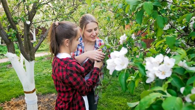 정원에서 일하고 나무를 돌보는 딸과 함께 젊은 어머니의 초상화.