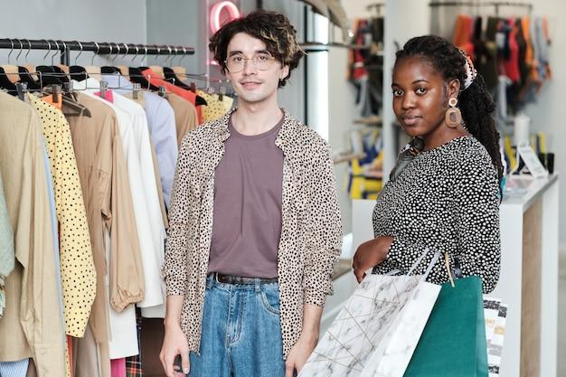 Портрет молодой многонациональной пары, смотрящей в камеру, вместе делая покупки в торговом центре