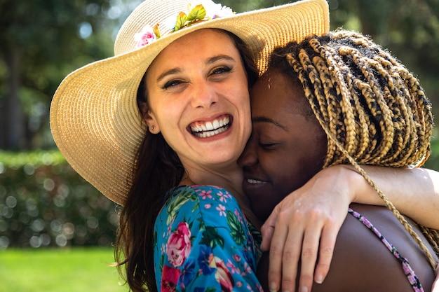 Lgbtのコンセプト夏を抱き締める愛の若い多民族レズビアンカップルの肖像画