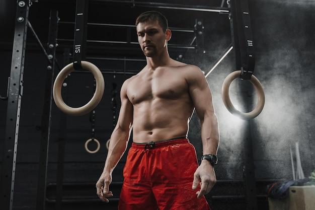 ジムでのトレーニングの準備をする若い筋肉クロスフィット選手のポートレート。