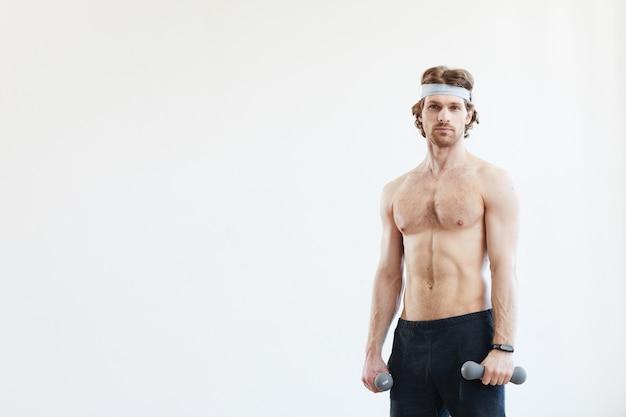 아령을 들고 흰색 배경에 대해 카메라를보고 젊은 근육 질의 남자의 초상화