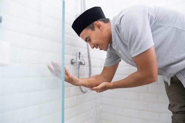 Портрет молодого мусульманина совершает омовение (омовение) перед молитвой дома