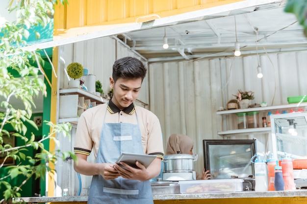 トラックのコンテナボックスで作られた彼の小さな店で食べ物や飲み物を売る若いイスラム教徒の男性の肖像画
