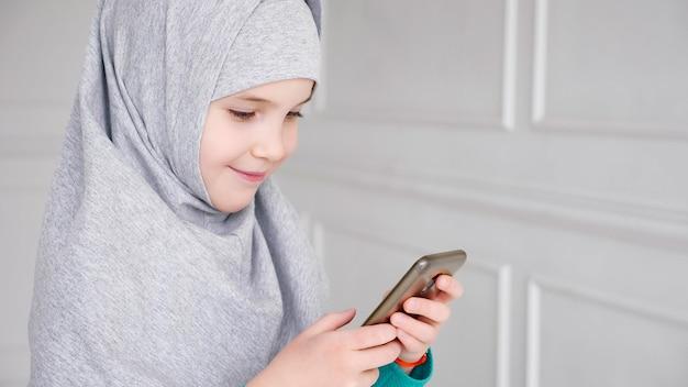 회색 히잡을 쓴 젊은 이슬람 십대 소녀의 초상화가 스마트폰, 측면 보기를 하고 있습니다.