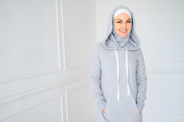 灰色のヒジャーブと自宅で国民のフィットネスドレスを着た若いイスラム教徒の女性の肖像画、コピースペース。
