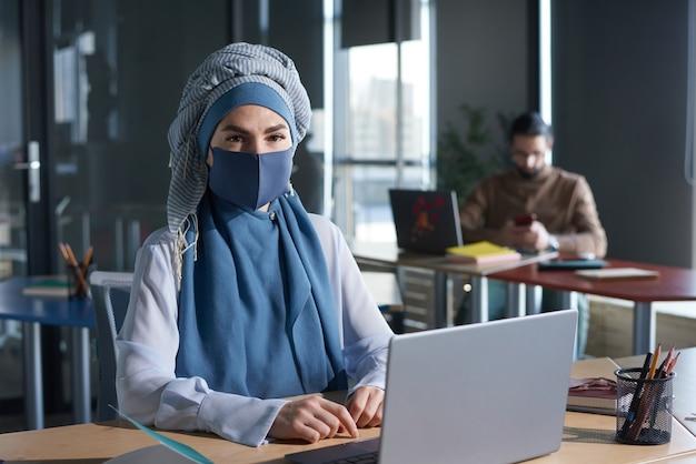 사무실에서 노트북으로 온라인 작업을 하는 동안 카메라를 보고 있는 히잡을 쓴 젊은 이슬람 여성의 초상화
