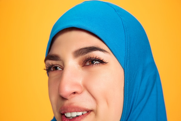 黄色のスタジオの背景に分離された若いイスラム教徒の女性の肖像画